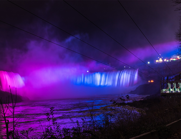 Horseshoe Falls at night lit in purple and blue
