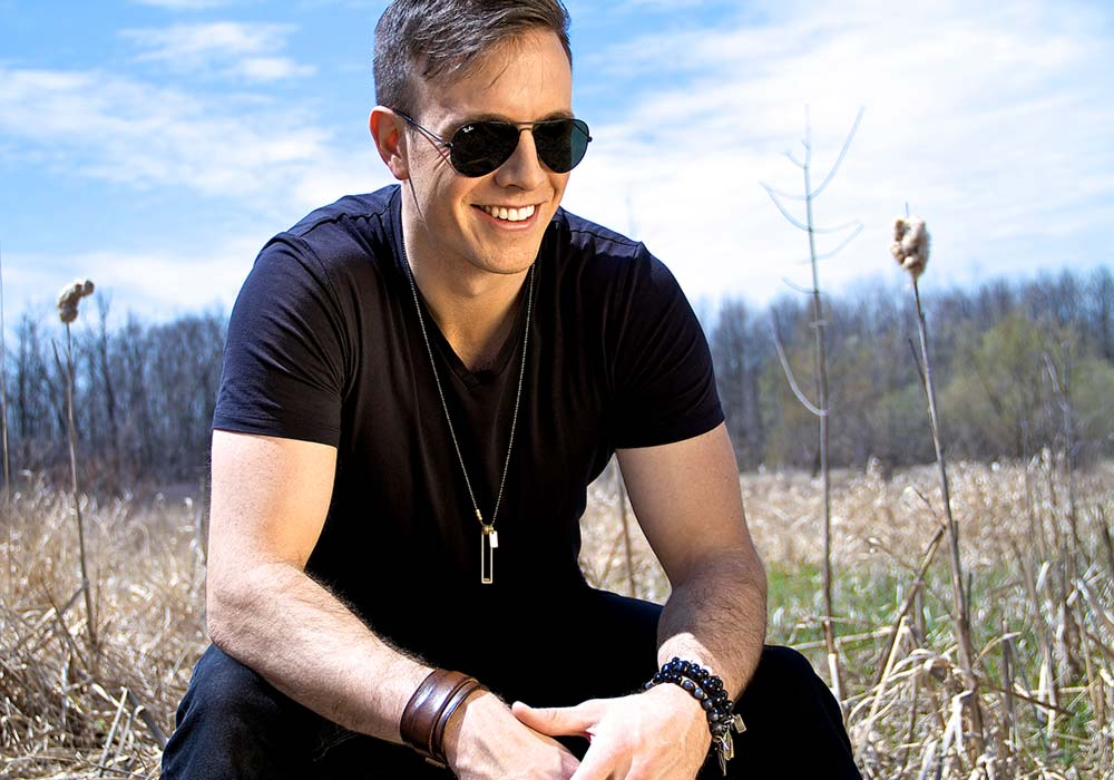 Eric Ethridge sitting in a field with sunglasses