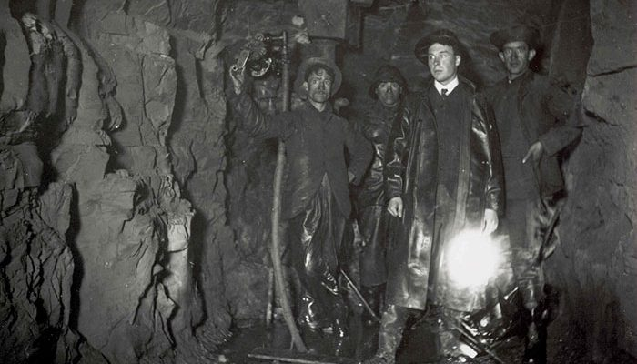 men with torch standing in dark tunnel