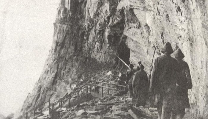 People walking down a stairway next to a cliff