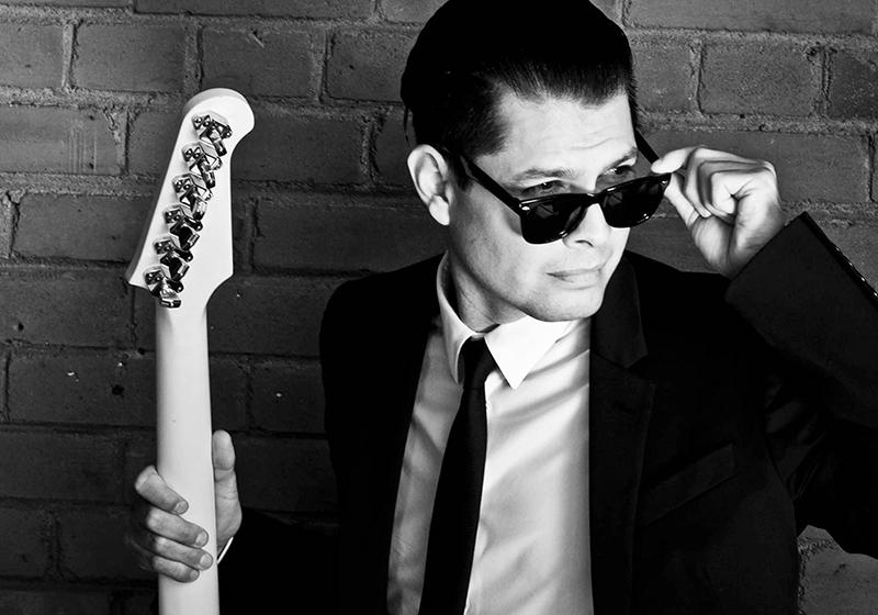 Artist Derek Miller holding a guitar