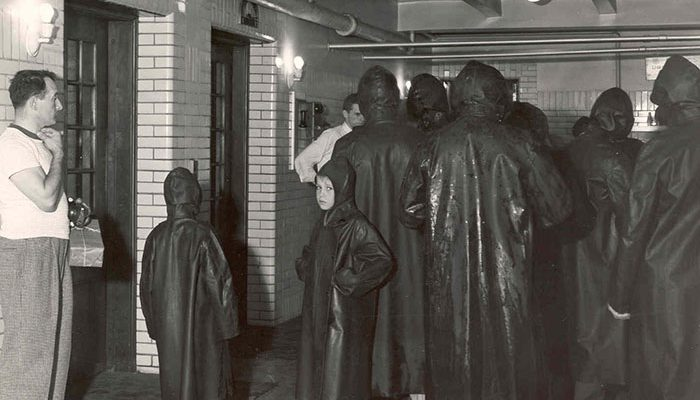 people standing with raincoats in a hallway