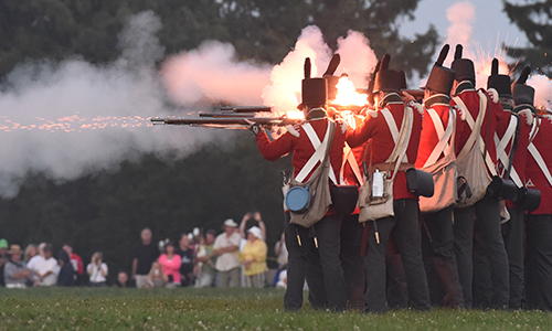 Soldiers firing muskets in a line