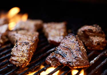 steaks cooking on a grill
