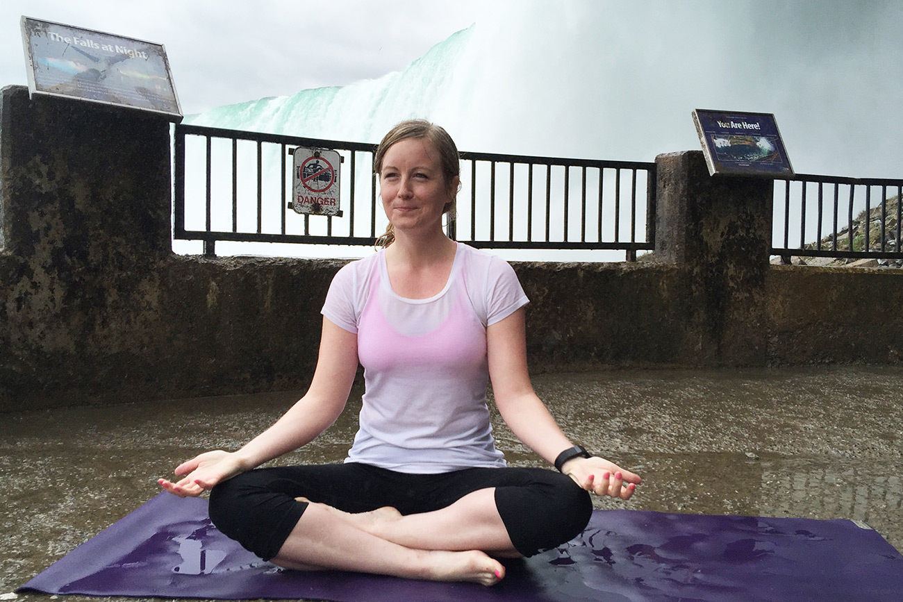 woman practicing yoga in front of waterfall