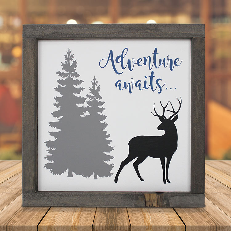 Rustic wooden sign with tree and deer